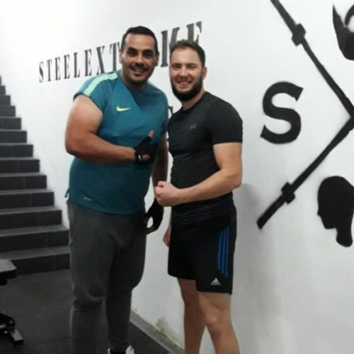 Image of personal trainer with member side by side